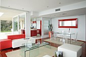 Open-plan interior with plexiglas and leather designer furniture, red accents and sliding door leading to kitchen in background