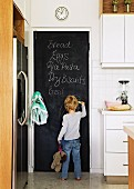 Young child drawing on chalkboard door