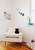 Soft toy sitting on elegant, white armchair in corner of child's bedroom below pinboard and bird ornaments on wall