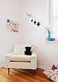 Eleganter, weisser Polstersessel mit Stofftier in Ecke eines Kinderzimmers, an Wand Memobord und Dekovögel