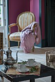 Silver coffee pot and two cups on side table in front of blanket on gilt armchair