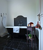 Clawfoot bathtub and small table in bathroom with black marble floor