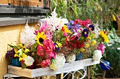 Colourful beakers of summer garden flowers