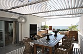 Rattan chairs around wooden table on terrace with slatted roof