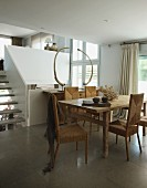 Wicker chairs around wooden dining table in front of foot of staircase