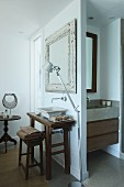 Tolomeo standard lamp next to rustic washstand with countertop basin; additional sink in niche with drawers in base cabinet
