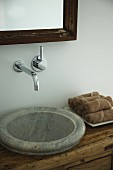 Rustic stone sink integrated into wooden chest of drawers with designer, wall-mounted taps