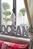 Ornamental letters on windowsill and view of trees in courtyard through window