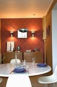 Retro-Esszimmer mit Designklassikern: Gedeckter Tisch vor Wand mit roter Ornament-Tapete und zwei Kommoden
