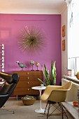 Wohnzimmer im Retrostil mit einer lilafarbenen Wand, Kunstobjekten und einem Eames Schaukelstuhl