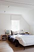 Elegantes weißes Sofa mit Antik-Flair vor Doppelbett in weißem Dachgeschossschlafzimmer mit Eichenparkett