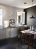 Retro pendant lamp above dining table made from glass table top on wooden trestles in simple kitchen with black accent wall