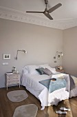 Double bed flanked by shabby-chic bedside cabinets and wall lamps; fan on stucco ceiling