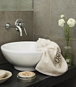 Wall-mounted tap above washstand with countertop basin; draped towel and flower arrangement
