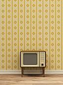 Retro Fernseher vor gelb gemusterter Tapete