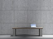 Laptop on bench against concrete wall