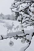 Zwei Rehfiguren aus Holz und weisse Weihnachtskugeln auf schneebedecktem Ast