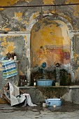 Wash area in shabby-chic interior, vintage zinc bowl on stone bench below water spouts in arched niche; Mediterranean, French style
