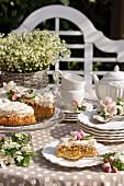 Apfelkuchen mit Baiserhaube, Kaffeegedeck und üppiger Maiglöckchenstrauß auf sonnigem Tisch im Freien