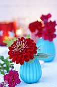 Zinnia and snap dragons in turquoise glass vases with lit candles in background