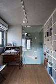 Office with antique bureau, fitted shelving and glass door leading to bathroom