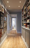 Narrow hallway with fitted cupboards and shelves below suspended ceiling with recessed spotlights in traditional interior