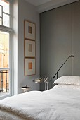 Bed with white bed linen against floor-to-ceiling panels covered in grey fabric in traditional, elegant interior