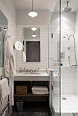 Marble washstand below mirror on white-tiled wall next to glass shower screen in small bathroom