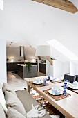 Set table with upholstered bench in front of open-plan kitchen in converted attic