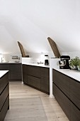 Custom kitchen counter with dark wooden drawer fronts fitted against sloping attic walls