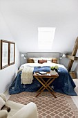 Blue bedspread on double bed below skylight in narrow bedroom