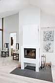 Grey tiled area around masonry log-burner, modern drawings on wall and dark antique chairs in background