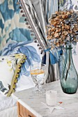 Dried hydrangea in glass vase and crystal drinking glass on marble-topped bedside cabinet next to bed with floral covers