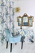 Pale blue velvet armchair at dressing table with valance below vintage three-part mirror on white wooden wall
