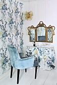 Armlehnstuhl mit hellblauem Samtbezug vor Schminktisch mit Husse und nostalgischem, dreiteiligem Spiegel an weisser Holzwand