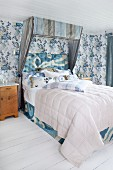 Half-tester double bed with striped canopy in romantic bedroom with blue floral wallpaper