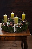 Rustic Advent wreath with four lit green candles decorated with walnuts, moss and pine cones