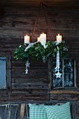 Rustic Advent wreath of fir branches hung in front of weathered wooden façade