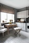 Dining area below window with rustic wooden table and stool in pale grey fitted kitchen