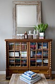 Mirror leaning against pale grey wall on top of antique, half-height, glass-fronted cabinet