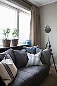 Dark grey sofa with scatter cushions and retro-style standard lamp below window