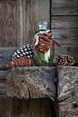Fir cone hand-crafted from brown felt tied to glass bottle