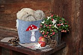 Balls of wool in hand-decorated felt basket with appliqué toadstool and Advent arrangement in rustic surroundings