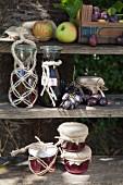 Flaschen und Marmeladengläser mit Makramee-Dekoration auf verwittertem Holzregal zur Erntezeit