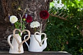 Garden flowers in white vintage jugs decorated with macrame hearts