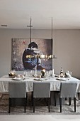 Festively set dining table below candle chandelier and modern artwork on wall