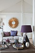 Purple table lamp on coffee table, sofa and sunburst mirror on wall