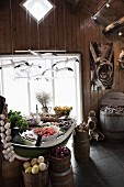 Vegetables in wooden containers on dining table below mobile of flying gulls in rustic interior