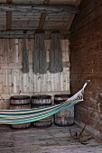 Hammock hanging from hook in rustic wooden wall