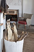 Dried fish in whitewashed wooden tub in front of fifties armchair in rustic interior